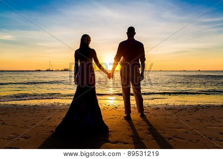 The Bride And Groom Are Kept Hands On A Tropical Beach . Silhouette Photo At Sunset .