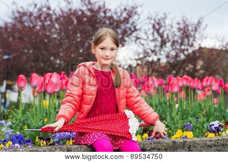 Outdoor portrait of a cute little girl of 7 years old, wearing bright pink jacket, holding umbrella