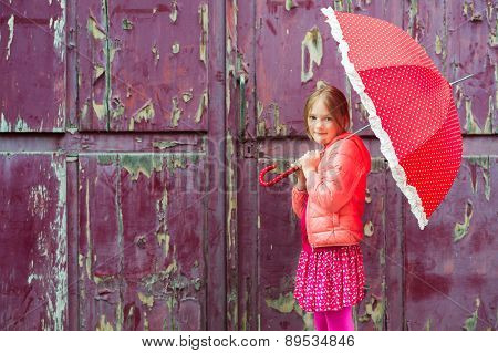 Portrait of a cute little girl with red umbrella