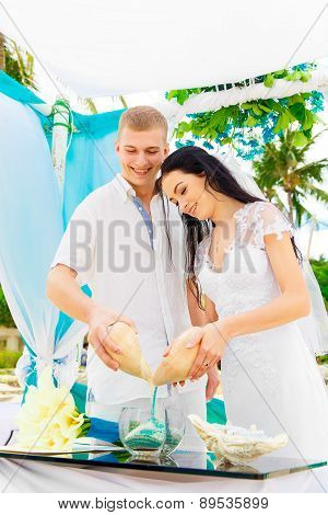 Wedding Ceremony On A Tropical Beach In Blue. Sand Ceremony. Happy Groom And Bride