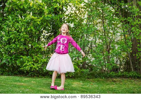 Adorable little girl spinning around in a beautiful park