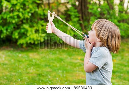 Cute little boy playing with slingshot, outdoors