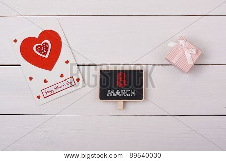 Blackboard With 8 March Tag, A Gift And A Card With Red Hearts On A White Table.