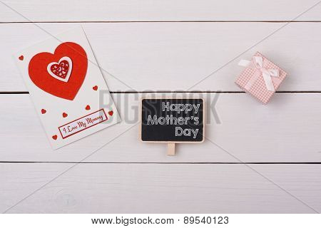 Blackboard With Happy Mathers Day Tag, A Gift And A Card With Red Hearts On A White Table.