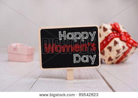 Happy Woman's Day Message Written On Little Chalkboar.