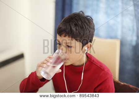 Young boy drinking glass of water