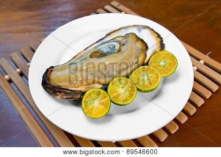 Opened Fresh Oyster In A White Plate With Lime On A Wooden Table