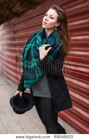 Portrait Of A Beautiful Girl In A Coat With A Scarf. Hat In Hand.