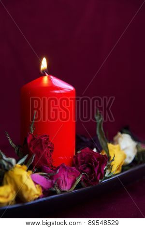 lighting candle with dry roses