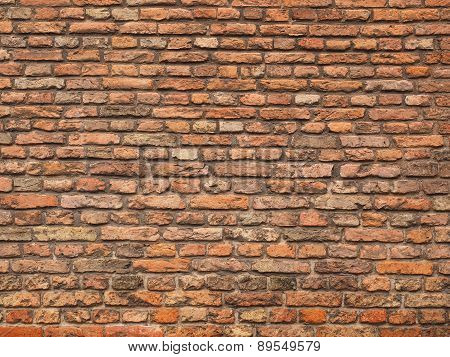 Medieval rough brick wall of small bricks