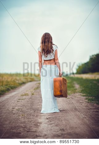 Young Woman With Suitcase In Hand Going Away By Field Road