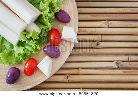 Heart of palm (palmito) with cherry tomato on cutting board