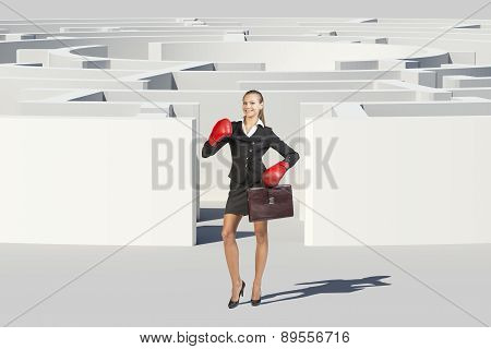 Businesswoman in boxer gloves looking at camera