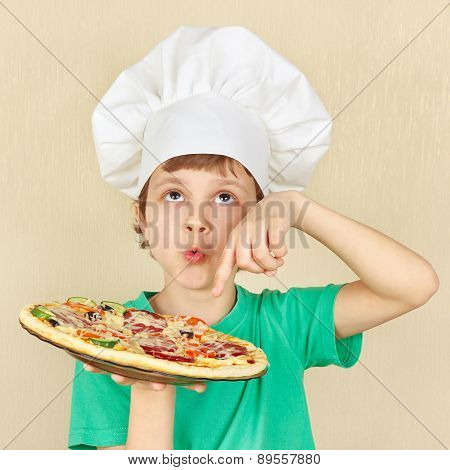 Young smiling kid in chefs hat with cooked appetizing pizza