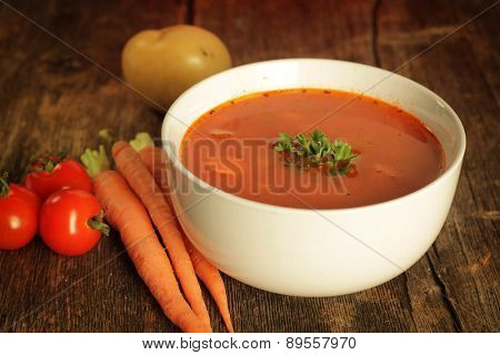 Vegetables soup surrounded by fresh vegetables on a rustic background