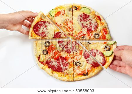 Hands of a man and a child are taking pieces of tasty pizza