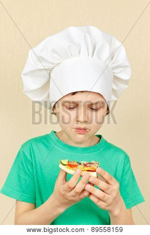 Little boy in chefs hat does not like taste of cooked pizza