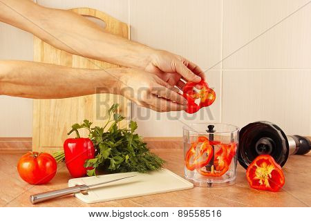 Hands cook put chopped red pepper in blender