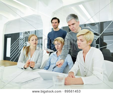 Team sitting in office with tablet computer at the desk