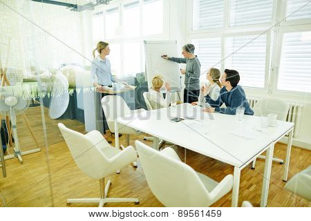 Man at flipchart in business meeting in a conference room