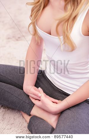 Woman sitting on carpet in lotus pose