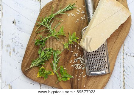 Parmesan Chess With Grater On Chopping Board And Fresh Herbs