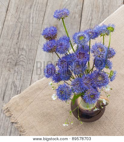 Rustic Still Life With A Bouquet Of Blue Flowers On A Wooden Background