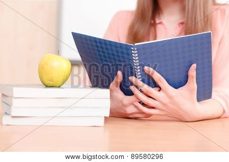 Woman holding blue copy book