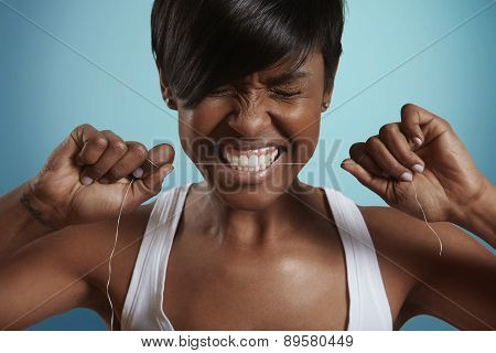 Woman Trying To Gnaw Through A Dental Floss, Blue Background