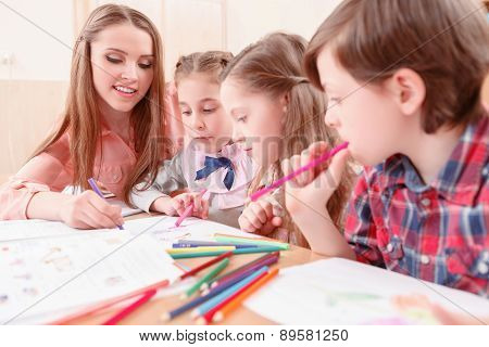 Young teacher drawing with pupils together