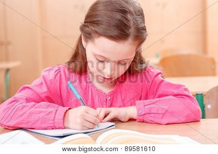 Little writing girl during classes