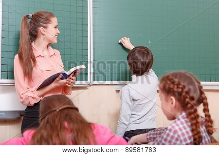 Teacher and pupil standing at blackboard