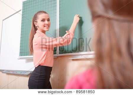 Young female teacher writing on blackboard.