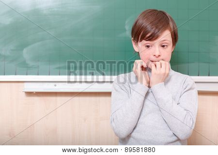Little thrilled pupil standing at blackboard.