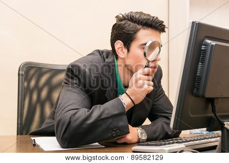 Businessman searching through magnifying glass in computer