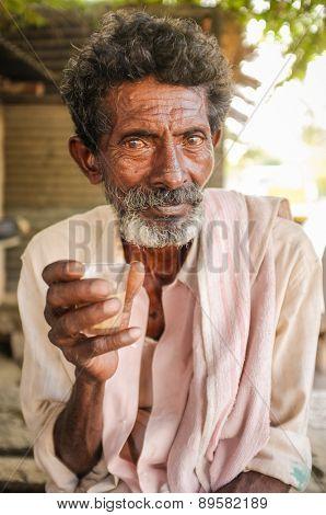 HAMPI, INDIA - 31 JANUARY 2015: Elderly Indian man holding a chai