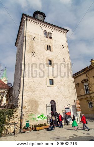 ZAGREB, CROATIA - 17 MARCH 2015: Lotrscak tower with its canon on a sunny day and tourists entering it.