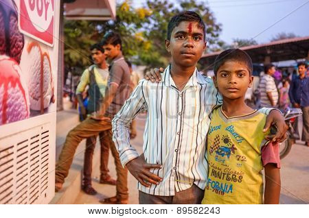 KAMALAPURAM, INDIA - 02 FEBRUARY 2015: Two Indian brothers hugging in street with people around them