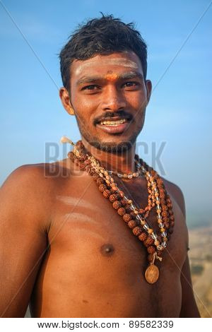 KAMALAPURAM, INDIA - 03 FEBRUARY: Indian pilgrim smiling  with religious necklaces and bindi on hilltop