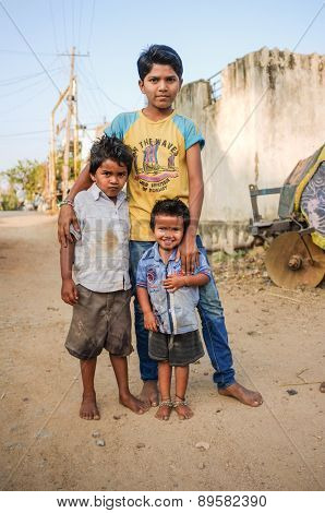 HAMPI, INDIA - 31 JANUARY 2015: Three young Indian boys standing in dusty street
