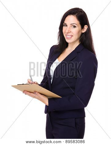 Brunette Businesswoman write on clipboard
