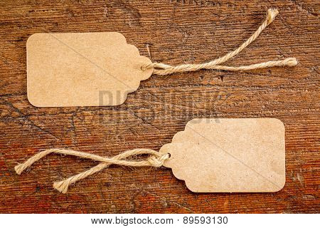 two blank paper price tags with a twine against rustic scratched wood