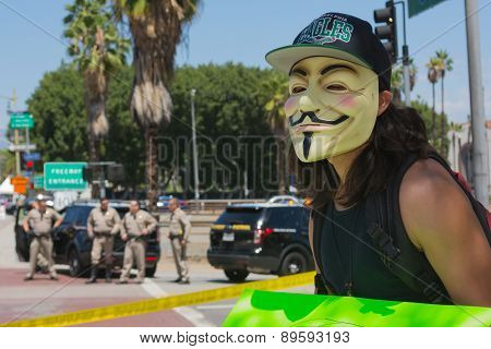 Anonymous With Mascara With Police In The Background