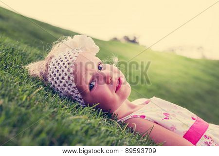 Little Beautiful Girl Lies On The  Green Grass. The Image Is Tinted And Selective Focus.