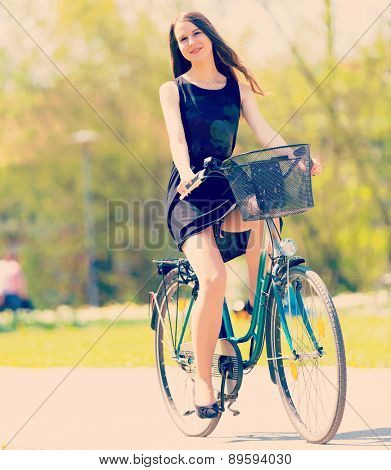 Young woman in short black dress with long hair rides a bicycle tour summer city park, look to camera. Toned Photo