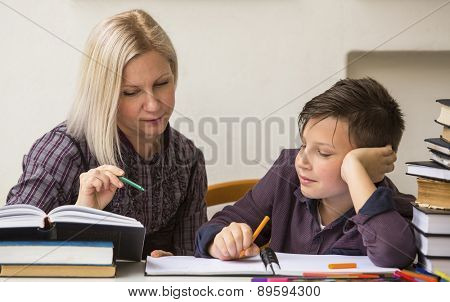 Schoolboy studying with the help of a tutor.