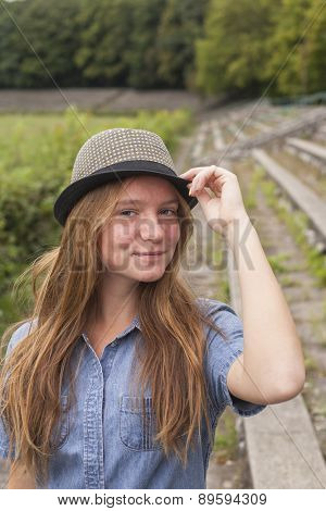 Young cute girl in the hat, outdoors outside the city.