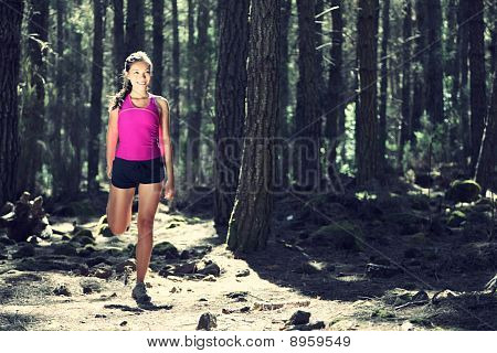 Woman Stretching During Training In Forest