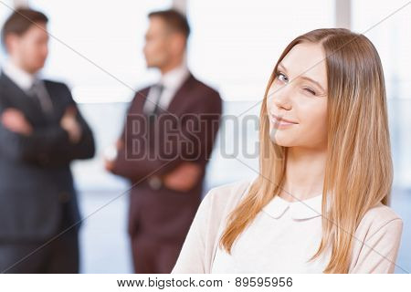 Blond young business woman standing in front of two men talking