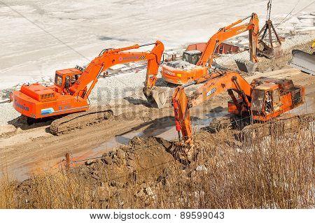 Excavators on pedestrian quay construction. Tyumen